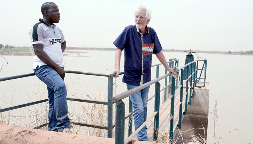 Two men standing on a raised platform overlooking a large water reservoir.