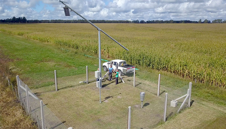 Monitoring station in Argentina located in a field seen from above; two people are working to readjust the equipment. A pick-up truck is parked nearby.