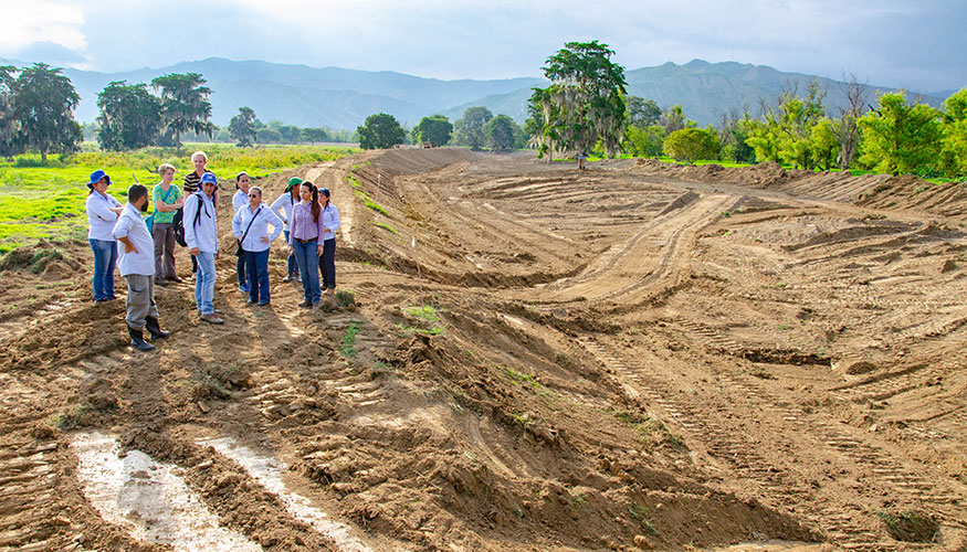 Group of people standing near the construction site for a water basin.
