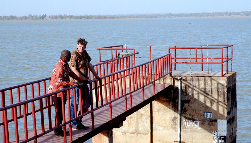 Two men standing on a platform overlooking a large body of water.