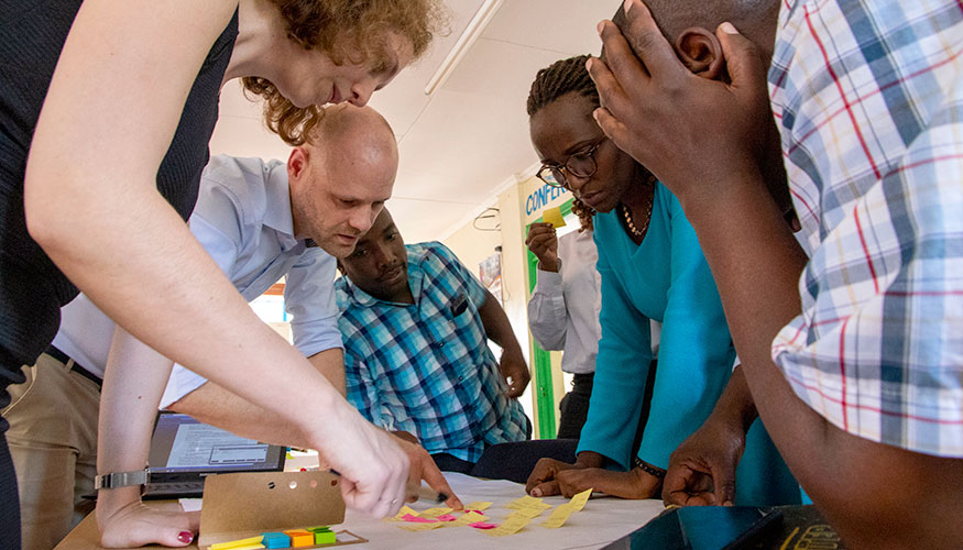 Group of people bending over a table. They are looking at a sheet of paper covered in Post-It notes.