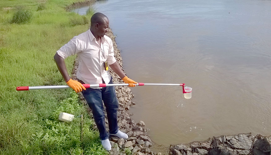 Man standing by water's edge. He is holding a cup with a water sample, which is attached to a short pole.