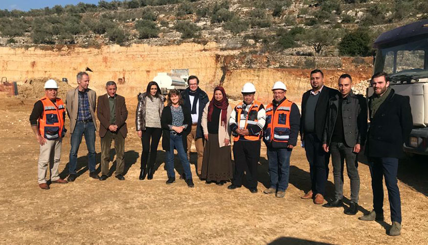 Outdoors group picture of Dutch Water Authorities team members and Palestinian partners during a visit at a building site.