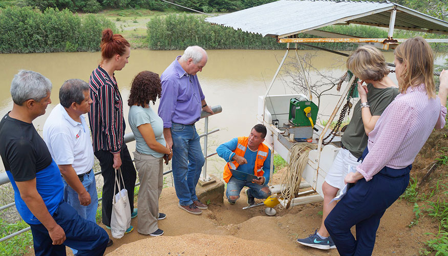 Group of people gathered round a water management device on the banks of a river in Peru. A man is showing them the workings of the device.