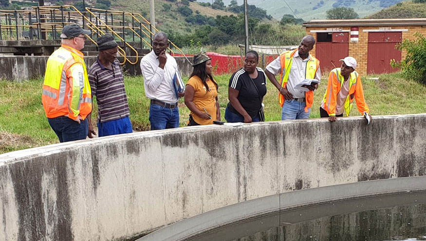 People standing next to a waste water reservoir during a Dutch Water Authorities field visit in South Africa.