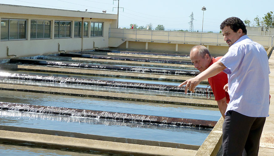 Two men inspecting a waste water treatment plant.