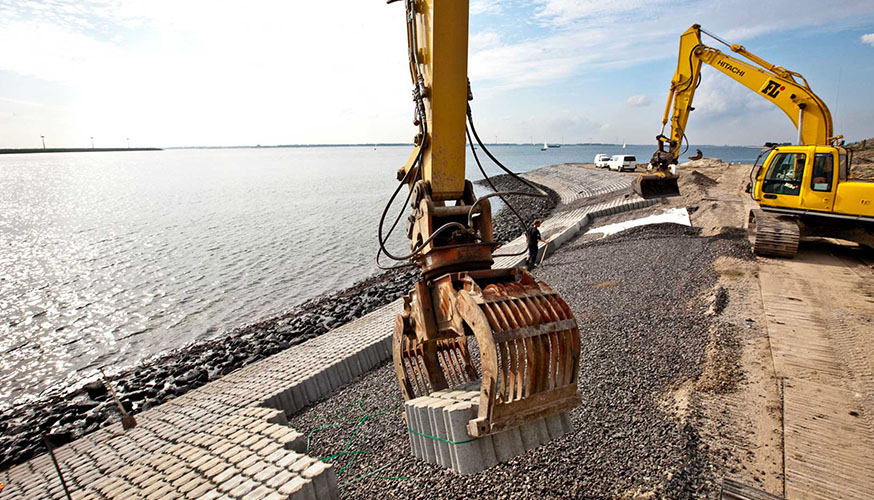 Large excavators placing concrete blocks on a dyke at the edge of a large body of water in the Netherlands..