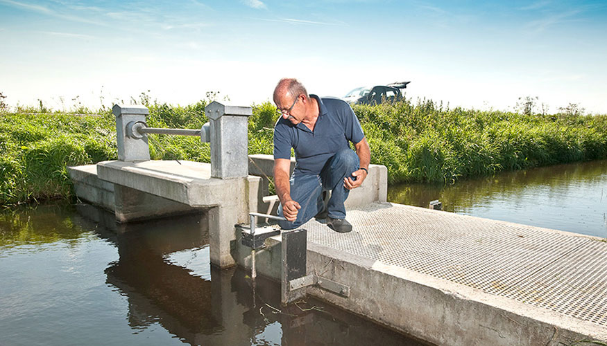 Regional water authority employee performing maintenance at a weir in the Netherlands.